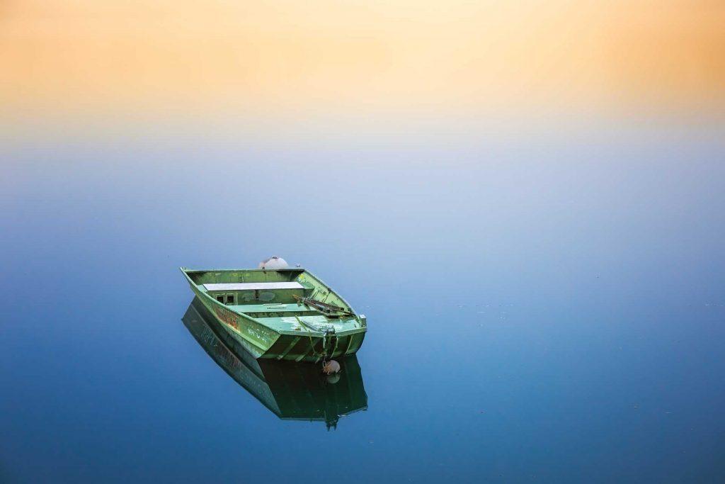 Groene boot op een meer voor een betere compositie