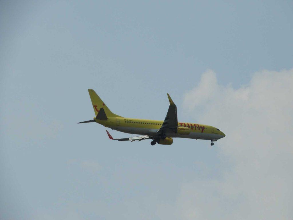 vliegtuig TUI in de lucht geel passagiers