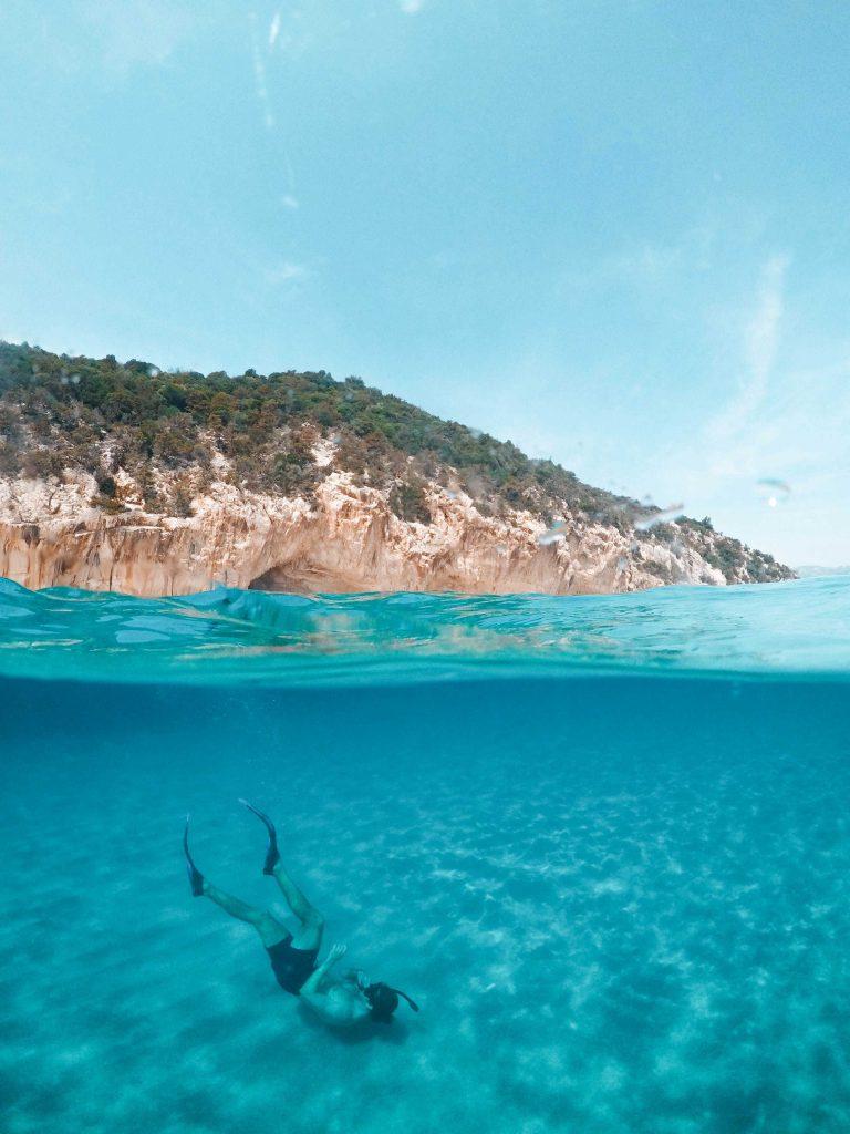 duiker in het blauwe water met snorkel