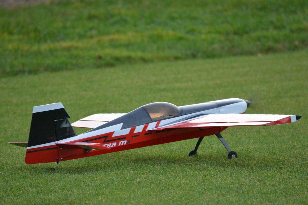 Rood-geel modelvliegtuig op het gras
