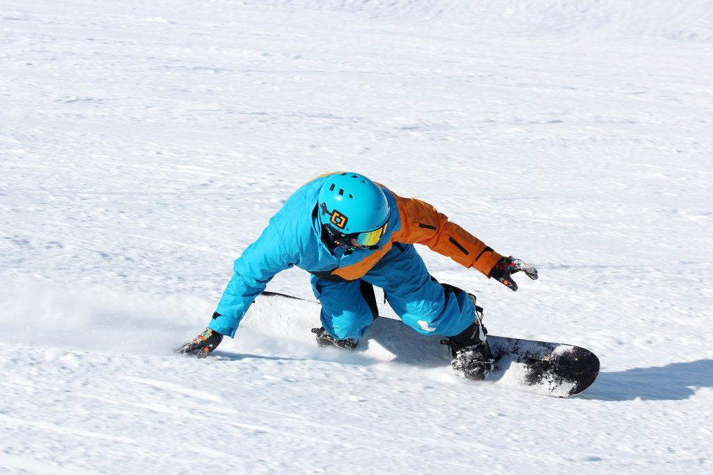 snowboarder in de sneeuw op de piste met zon