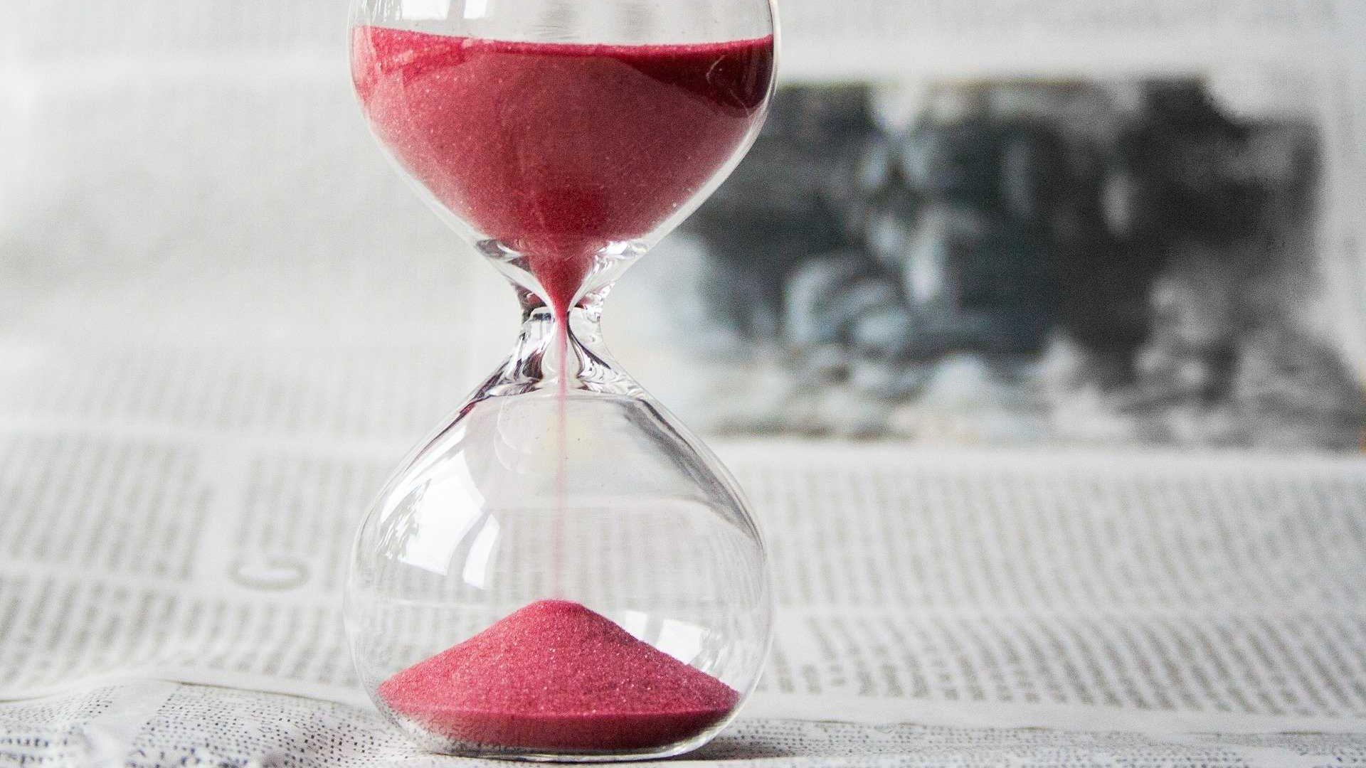 roze zandloper glas op tafel krant