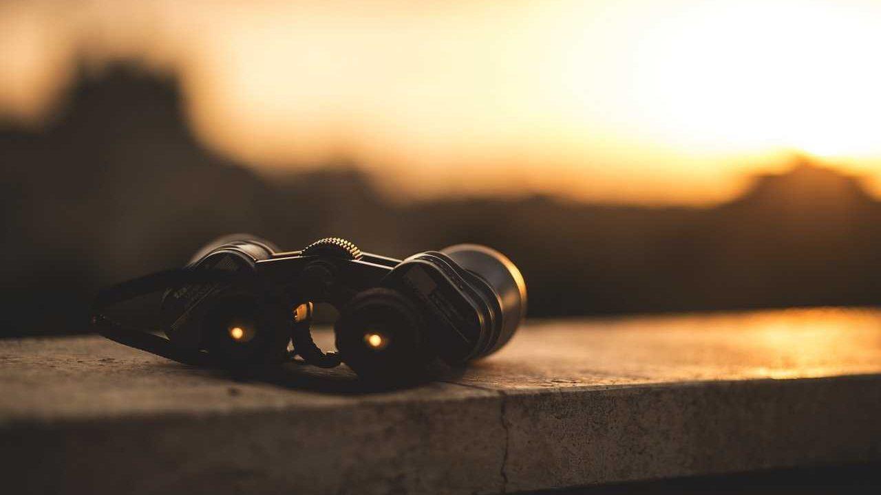 verrekijker op tafel zonsondergang zwart