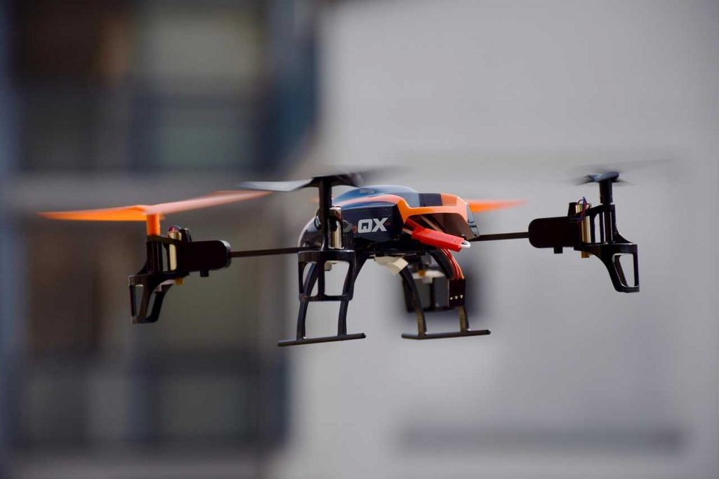 Speelgoeddrone in de lucht oranje
