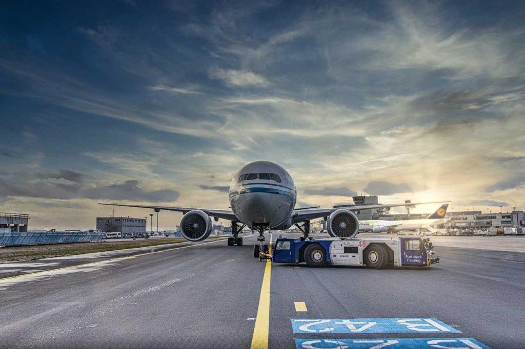 blauwe witte vliegtuig op vliegveld van voren